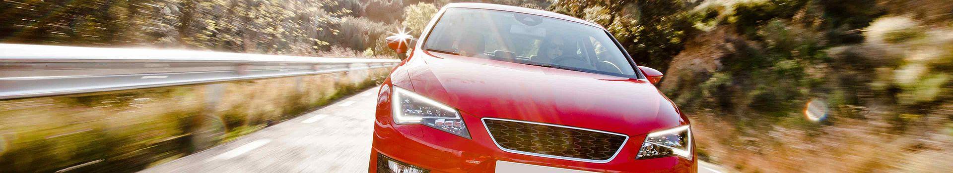 Visual zu den Einsatzbereichen Auto: Rotes Auto in Frontansicht und voller Fahrt.